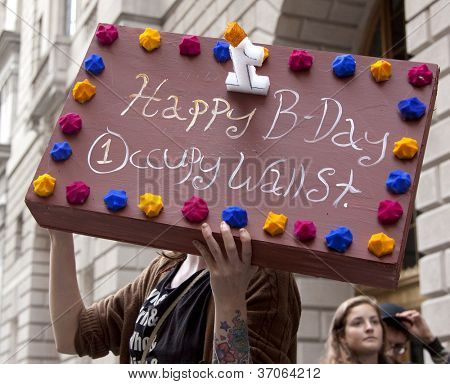 NEW YORK - SEPT 17: A protester holds a sign that looks like a birthday cake that reads 'Happy B-Day Occupy Wall St' on the 1yr anniversary of the protests on September 17, 2012 in New York City, NY.