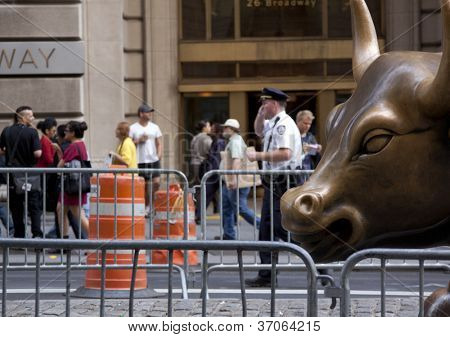 NEW YORK - SEPT 17: A policeman stands in front of the Charging Bull statue in lower Manhattan on the 1yr anniversary of the Occupy Wall St protests on September 17, 2012 in New York City, NY.