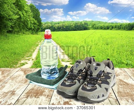 Sport shoes, towel and water in bottle on wooden boards and field with sky on background
