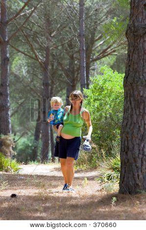 Joven madre llevando a su hijo y caminando por el bosque