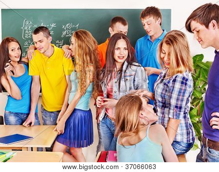 Group happy student near green  blackboard in classroom.