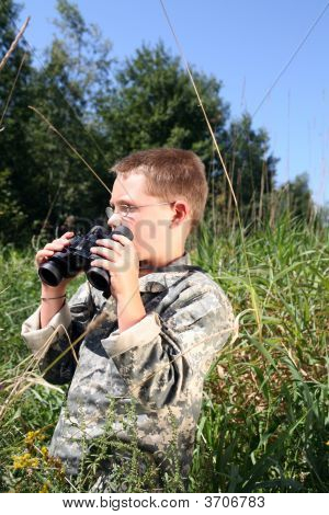 Child In Camouflage Holding Binoculars In The Grass
