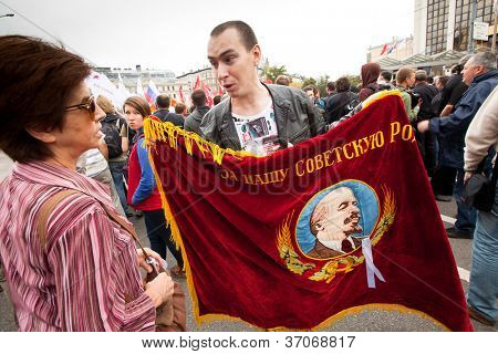 MOSCOW - 15 SEPTEMBER: An opposition supporter holds a Soviet era flag showing a portrait of Lenin and reading For our Soviet motherland as he takes part in a protest rally on Sept.15, 2012 in Moscow.