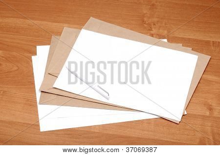 stack of envelopes on a brown table