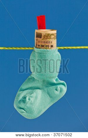 baby socks on clothesline with yen bills from japan.