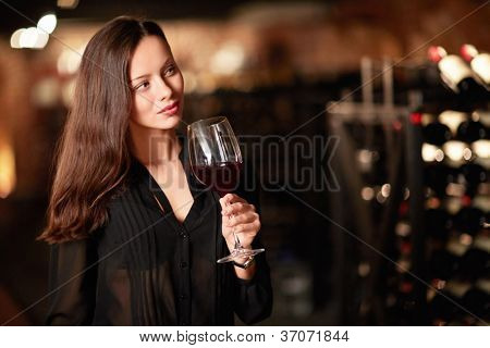 Young girl with a glass of wine in the cellar