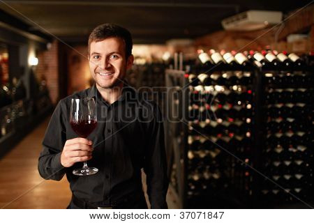 Man with a glass of wine in the cellar