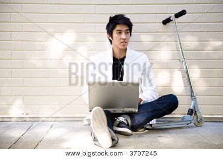 Young Casual Asian Man With Laptop