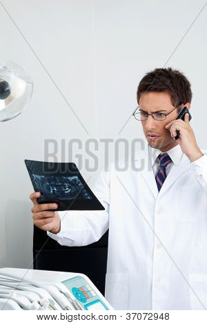 Young male doctor looking at X-ray report while using mobile phone in dental clinic
