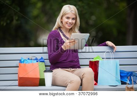 Portrait of pretty young woman with shopping bags using tablet PC on park bench