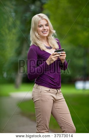 Portrait of a beautiful young woman holding smart phone in park