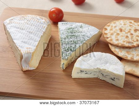 From left: St Albry, a herbed brie and blue-veined camembert, with crackers and cherry tomatoes on a cheeseboard.