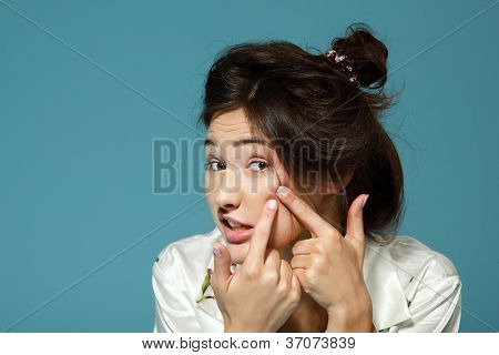 Teen girl with problem skin look at pimple. Morning theme. Over blue background.