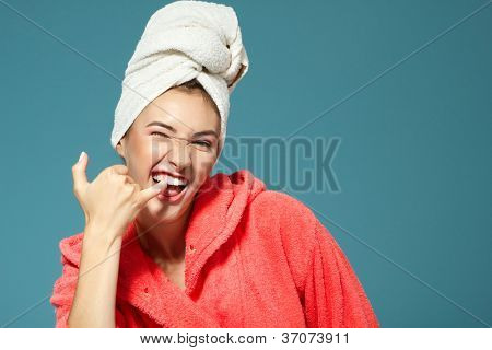 Cheerful attractive funny teen girl clean her teeth in the morning. Over blue background.