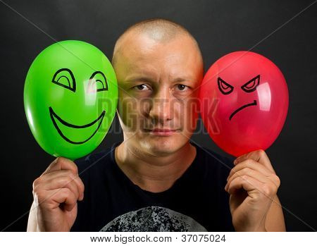 Emotionless man between happy and angry balloons