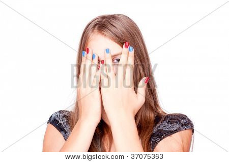 Teenage girl playing hide-and-seek and peek through fingers, isolated on white