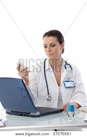 Portrait of female doctor sitting at desk at work, using laptop computer and mobile phone, smiling.