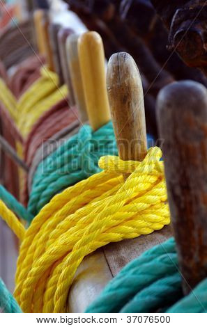 Colorful ropes wrapped around belaying pins in a sailing ship
