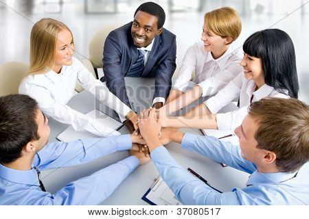 View from above of business team making pile of hands on working place