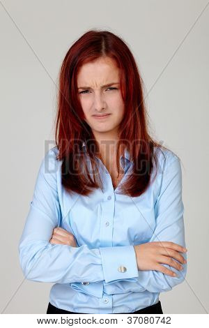 Portrait of angry pretty business woman standing with hands folded in blue shirt, isolated on grey