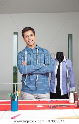 Portrait of young male tailor standing arms crossed with mannequin in background