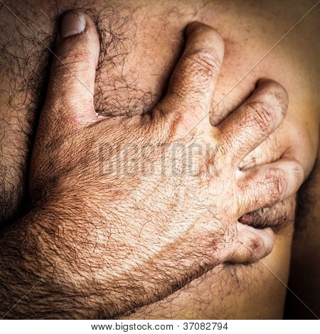 Close up of a hand grabbing the chest of a man who is suffering a heart attack