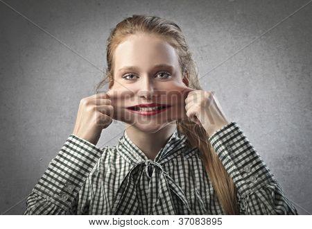 Beautiful blonde girl pulling her cheeks
