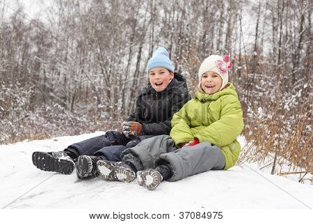 Smiling brother, sister seat on saucer in winter forest
