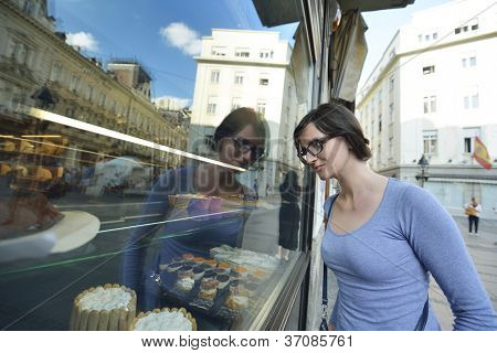 urban scene of young woman in front of sweet candy food store window