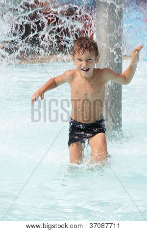 young happy child boy having fun in water
