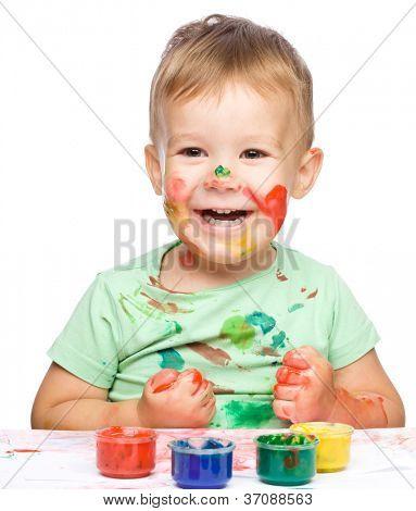 Bildnis eines niedlich kleinen Knaben spielen mit Farben, die Pressen seine Fäuste in Freude, isolated over white