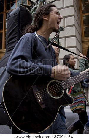 NEW YORK - SEPT 17:  A protester plays his guitar and sings while walking up Broadway during on the 1yr anniversary of the Occupy Wall St protests on September 17, 2012 in New York City, NY.