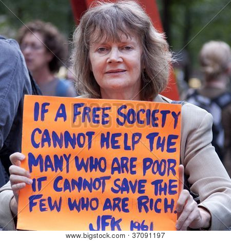 NEW YORK - SEPT 17: A protester holds a sign with a quote from JFK as she stands in Zuccotti Park on the 1yr anniversary of the Occupy Wall St protests on September 17, 2012 in New York City, NY.