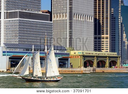 Sailboat passes Financial District buildings in New York City's borough of Manhattan.