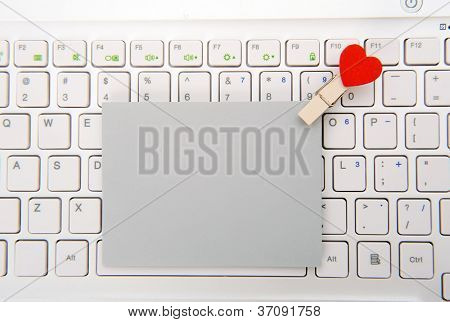 Laptop keyboard with small red hearts clothes pegs and sticky note
