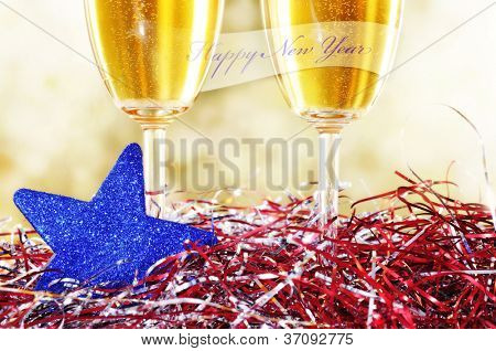 a pair of glasses of champagne with the sentence happy new year and some christmas ornaments