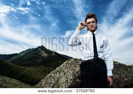Successful business man standing on a peak of the mountain.