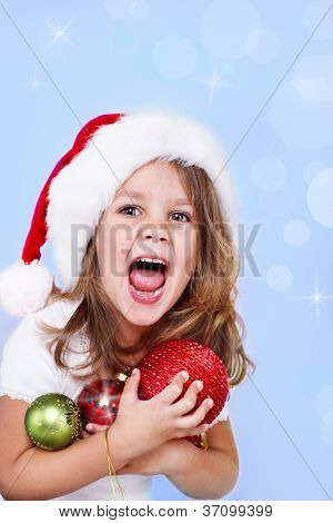 Portrait of a shouting girl in Santa hat holding Christmas decoration in hands