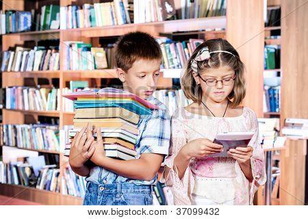Junge mit Bücher-Stapel und Mädchen mit e-reader