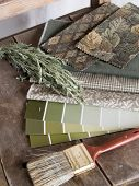 foto of sagebrush  - Earthy green tone paint sample cards fabric swatches and a paintbrush on a rustic unpainted chair with a twig of sagebrush - JPG