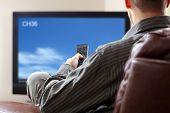 Man sitting on a sofa watching tv holding remote control