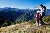 stock photo of italian alps  - Man and young boy standing in a mountain meadow - JPG