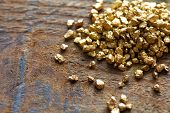 stock photo of trade  - a mound of gold on a old wooden work table - JPG