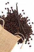 Coffee beans in a hessian drawstring sack and loose with vanilla pods over white background.