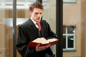 stock photo of court room  - Lawyer with civil law code in a court room - JPG