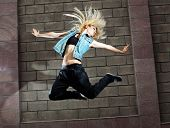 Teenage girl dancing hip-hop over the street wall