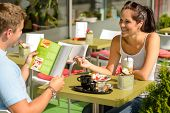 stock photo of frappe  - Couple eating looking at menu cafe restaurant smiling woman - JPG