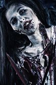 Close-up of a bloodthirsty zombie standing at the night cemetery. poster