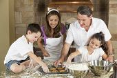 An attractive smiling family of mother, father, and two children baking and eating fresh chocolate c