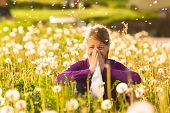 stock photo of allergies  - Girl sitting in a meadow with dandelions and has hay fever or allergy - JPG